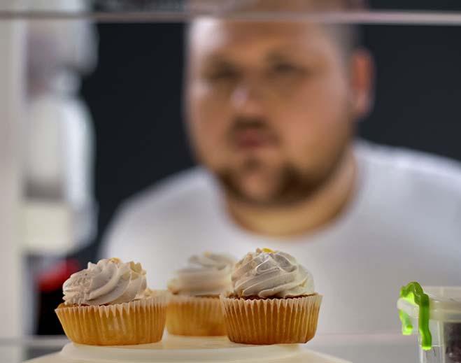 man looking at three cupcakes